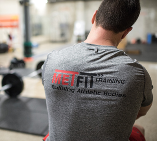 man with a met-fit logo on the back of his t-shirt