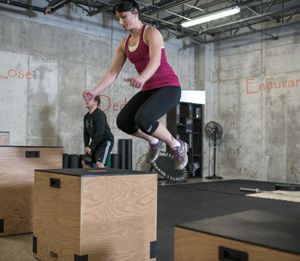 woman jumping onto a box